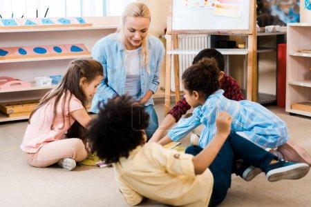 Foto de Enfoque selectivo de profesores y niños que juegan al juego en el suelo en la escuela montessori. - Imagen libre de derechos