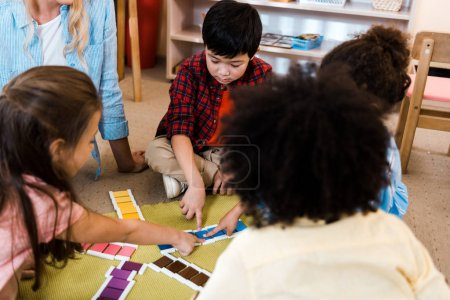 Photo for Selective focus of kids folding colorful game by teacher on floor in montessori school - Royalty Free Image