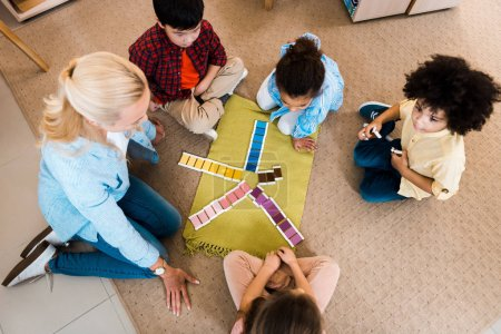 Photo for Overhead view of teacher playing with kids educational game on floor in montessori class - Royalty Free Image