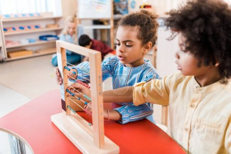 Photo for Selective focus of african american kids playing with scores with teacher and child at background in montessori school - Royalty Free Image