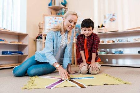 """Photo pour Orientation sélective d'un enfant asiatique jouant à un jeu éducatif avec un enseignant à l """"école de montessori - image libre de droit"""