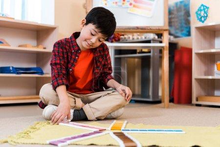 Photo pour Selective focus of child folding colorful game on floor in montessori school - image libre de droit