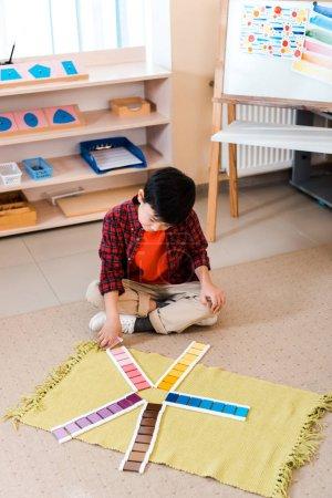Photo pour Vue grand angle de gamin asiatique jouant jeu éducatif sur le tapis à l'école montessori - image libre de droit