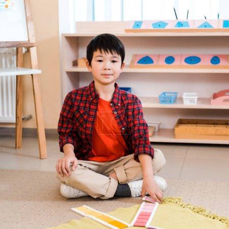Photo pour Un enfant asiatique regarde une caméra tout en pliant un jeu coloré sur le plancher d'une école de montessori - image libre de droit