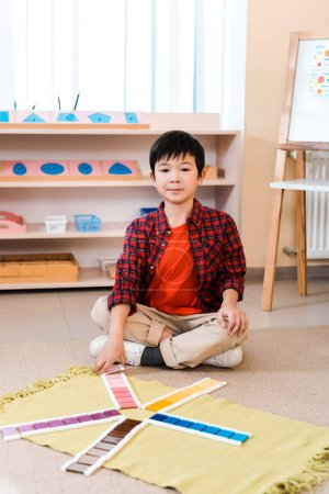 Photo for Child looking at camera while playing educational game on floor in montessori school - Royalty Free Image