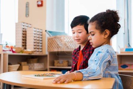 Photo pour Side view of children folding educational game in montessori school - image libre de droit