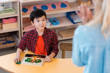 Photo pour Selective focus of asian kid looking at teacher in montessori school - image libre de droit