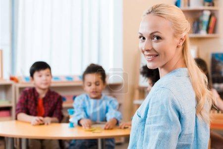 Photo pour Orientation sélective de l'enseignant souriant regardant la caméra avec les enfants à l'arrière-plan dans l'école montessori - image libre de droit