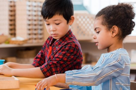 Photo for Side view of kids playing educational game during lesson in montessori school - Royalty Free Image
