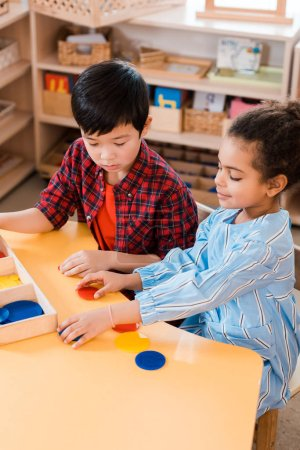 Photo for High angle view of kids folding colorful game during lesson in montessori school - Royalty Free Image
