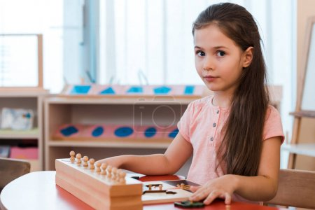 Photo for Child folding educational game and looking at camera at desk in montessori school - Royalty Free Image
