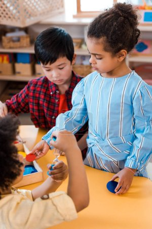 Photo for Selective focus of kids with hourglass and board game during lesson in montessori school - Royalty Free Image