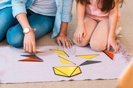 Photo pour Vue recadrée d'un enfant et d'un enseignant jouant à un jeu éducatif sur le sol en classe montessori - image libre de droit