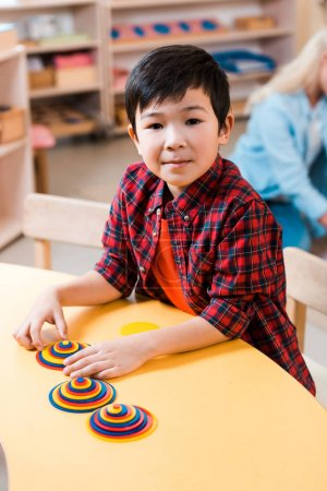 Photo for Selective focus of asian kid looking at camera while playing at desk in montessori school - Royalty Free Image