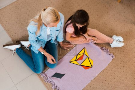Photo for Overhead view of teacher and kid sitting on floor by colorful game in montessori class - Royalty Free Image