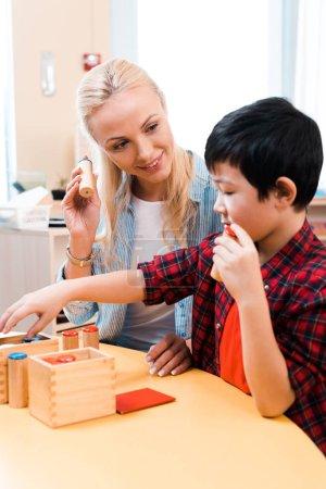 Photo pour Orientation sélective d'un enseignant souriant regardant un enfant asiatique pendant un cours à l'école de montessori - image libre de droit