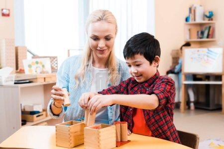 Photo pour Enfant asiatique jouant jeu de société en bois en souriant professeur au bureau de l'école montessori - image libre de droit