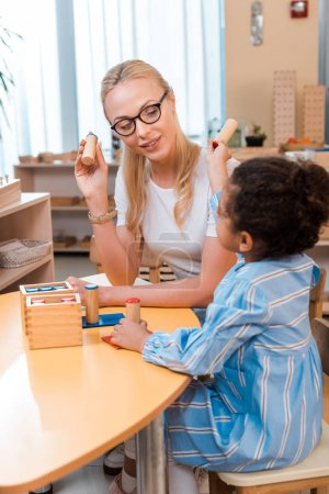 Photo for Child and teacher playing wooden board game at desk in montessori school - Royalty Free Image