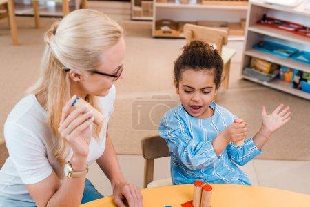 Photo pour Un enseignant joue à un jeu éducatif avec un enfant à la table dans l'école de montessori - image libre de droit