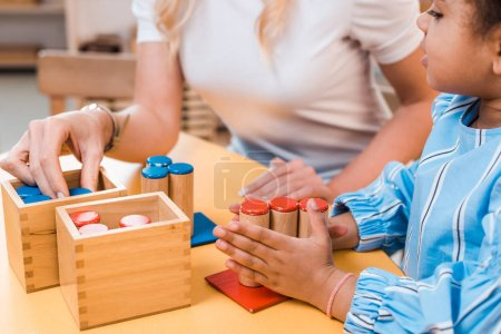 Photo for Selective focus of kid and teacher playing educational game at desk in montessori school - Royalty Free Image