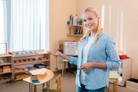Photo pour Attrayant sourire enseignant point avec la main et en regardant la caméra dans l'école montessori - image libre de droit