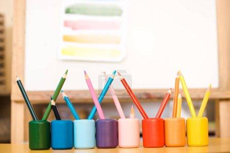 Foto de Enfoque selectivo de lápices de colores sobre la mesa con dibujo a bordo en segundo plano. - Imagen libre de derechos