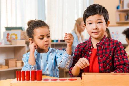 Foto de Enfoque selectivo de niños con juegos de mesa en la mesa de trabajo con profesores y niños de fondo en la clase montessori. - Imagen libre de derechos