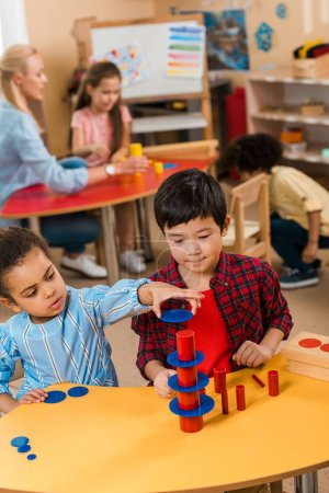 Foto de Enfoque selectivo de niños jugando durante la clase en la escuela montessori con niños y profesores de fondo. - Imagen libre de derechos