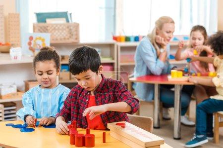 Foto de Enfoque selectivo de niños que juegan con niños y profesores en la escuela montessori. - Imagen libre de derechos