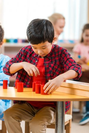 Photo pour Selective focus of asian kid folding educational game with teacher and children at background in montessori class - image libre de droit