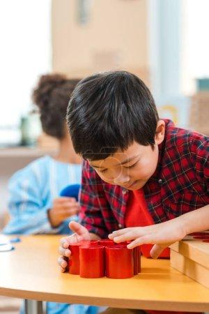 Photo pour Orientation sélective d'un enfant asiatique jouant au jeu de bois avec un enfant pendant une leçon à l'école de montessori - image libre de droit
