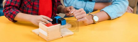 Photo pour Vue recadrée de l'enseignant et de l'enfant jouant des blocs de construction au bureau de la classe montessori, vue panoramique - image libre de droit