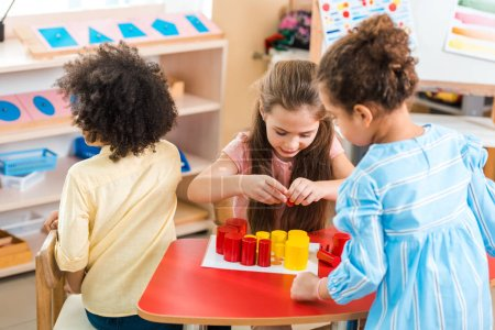 Photo for Children playing colorful educational game at desk in montessori school - Royalty Free Image
