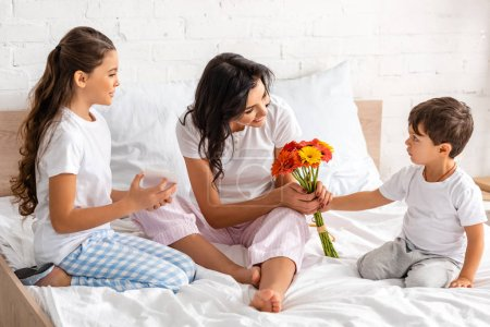 Photo for Smiling sister looking at cute brother presenting flowers to mom while sitting in bed on mothers day - Royalty Free Image