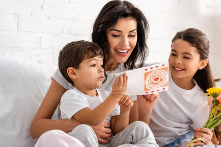 Photo for Happy woman reading mothers day card while sitting in bed with adorable children - Royalty Free Image