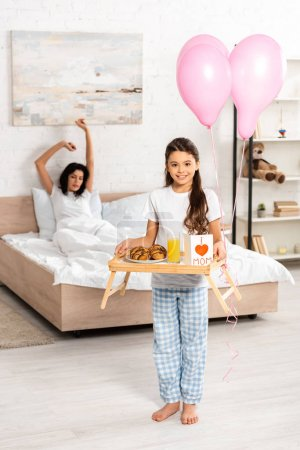 Photo for Cute daughter holding tray with breakfast, mothers day card with heart sign and mom lettering, while mother stretching in bed - Royalty Free Image