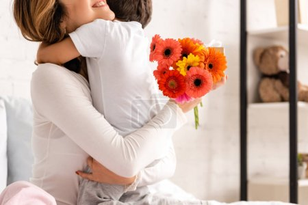 Photo for Cropped view of happy mother hugging son while holding flowers on mothers day - Royalty Free Image