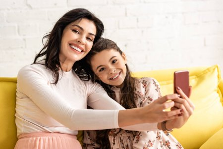 Photo for Happy mother and daughter smiling at camera while taking selfie on mothers day - Royalty Free Image
