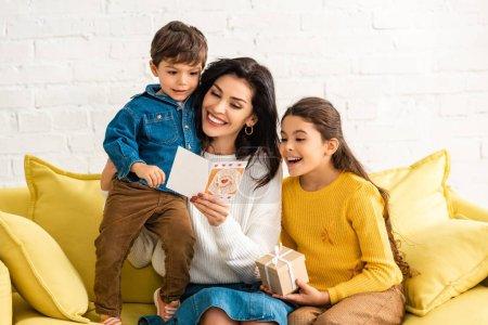 Photo pour Happy woman tenant la carte de maman et embrassant son fils, tandis que la fille tient une boîte-cadeau - image libre de droit