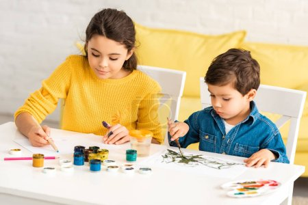Photo for Attentive, adorable children sitting at table and drawing with paints together - Royalty Free Image