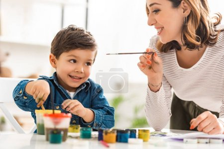 Photo for Cheerful mother and son holding paintbrushes near containers with paints - Royalty Free Image