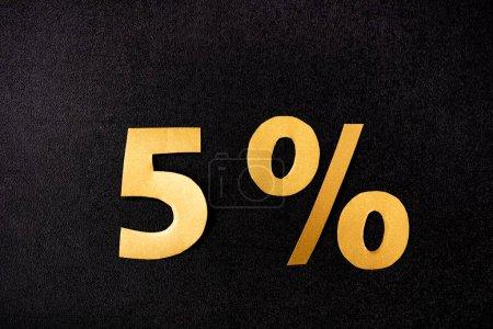 Photo pour Vue de dessus des signes dorés de 5 pour cent sur fond noir - image libre de droit