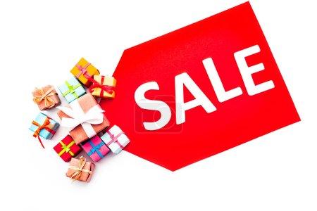 Photo pour Vue du haut de l'étiquette de prix rouge avec lettrage de vente près de cadeaux isolés sur blanc - image libre de droit