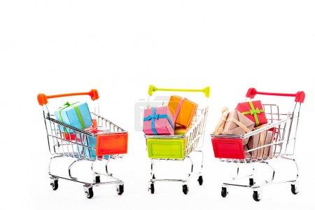 Photo pour Petits chariots décoratifs avec boîtes-cadeaux isolées sur blanc - image libre de droit