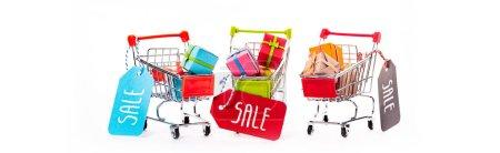 Photo pour Petits chariots décoratifs avec boîtes-cadeaux et étiquettes de prix avec lettrage de vente isolés sur pellicule panoramique blanche - image libre de droit