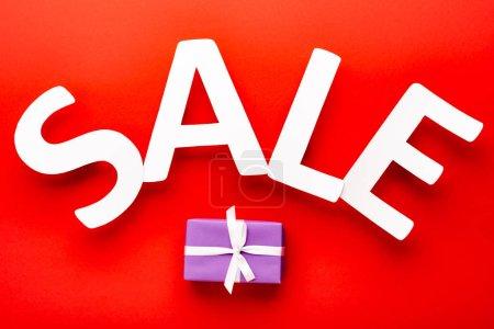Photo pour Vue du dessus de la vente blanche lettrage près de la boîte cadeau sur fond rouge - image libre de droit