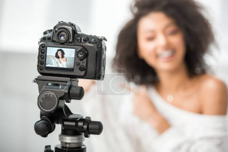 Photo for Selective focus of digital camera with happy african american influencer in braces pointing with finger at credit card on display - Royalty Free Image