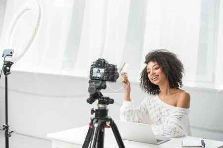 Photo for Selective focus of happy african american influencer in braces holding credit card near laptop and looking at digital camera - Royalty Free Image