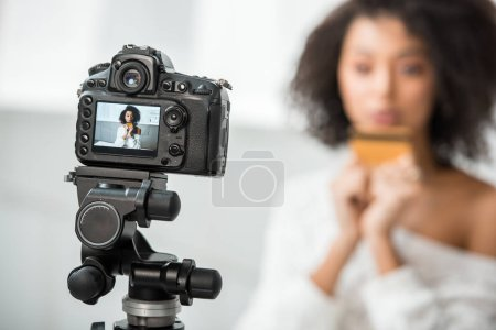 Photo for Selective focus of digital camera with african american video blogger holding credit card on display - Royalty Free Image
