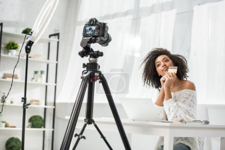 selective focus of young african american influencer holding credit card near laptop and looking at digital camera
